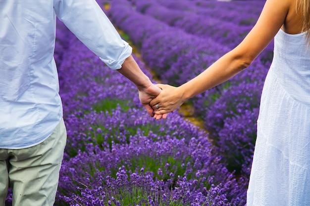 Para trzymająca się za ręce na lawendowym polu
