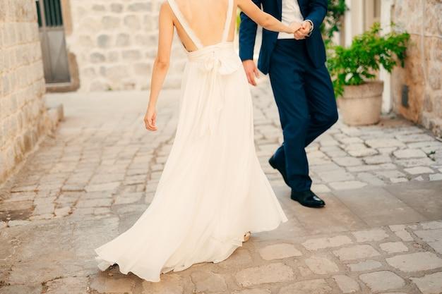 Para trzymająca się za ręce na starym mieście świeżo poślubiona para