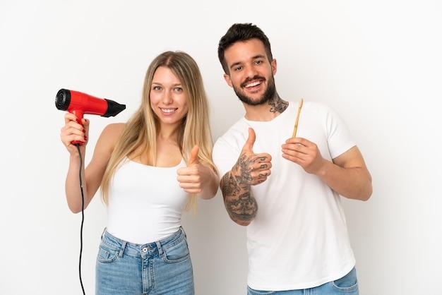 Para trzymająca suszarkę do włosów i szczotkująca zęby na białym tle, pokazująca kciuk w górę, ponieważ stało się coś dobrego