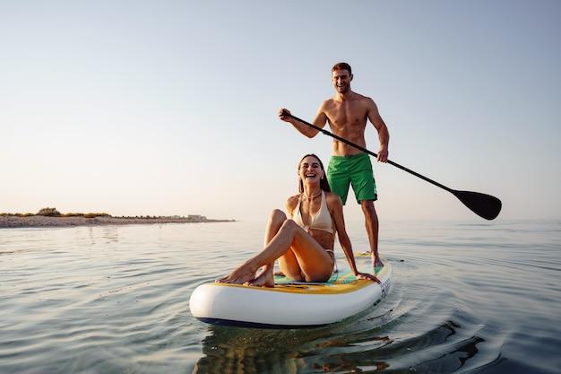 Para turystów młody mężczyzna i kobieta bawią się w paddleboardingu na morzu