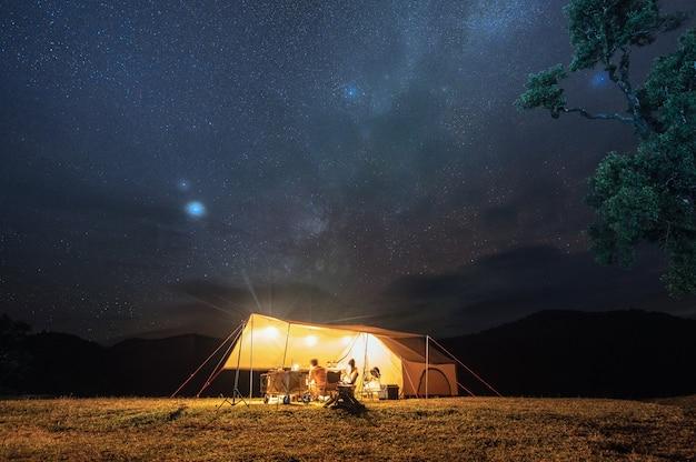 Para turystów odpoczywa w żółtym namiocie na wzgórzu z rozgwieżdżonym nocnym niebem w parku narodowym