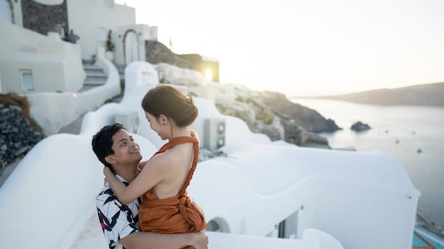 Para turystów odwiedzających bieloną wioskę w oia na santorini w grecji. morze śródziemne.