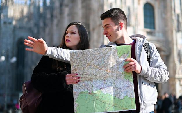 Para turystów w mieście, patrząc na mapę i dyskutując o następnym miejscu docelowym