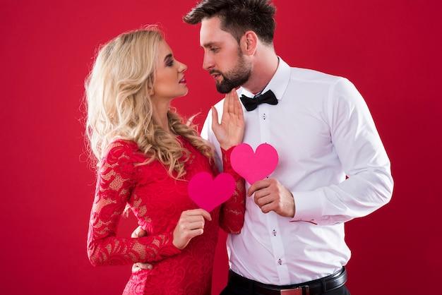 Para twarzą w twarz trzymając papierowe serca