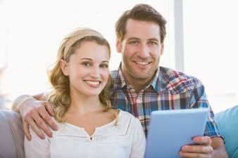 Para używa pastylka komputer osobistego na leżance podczas gdy patrzejący kamerę w jaskrawym żywym pokoju