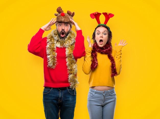 Para ubrana na święta bożego narodzenia z niespodzianką i zszokowany wyraz twarzy