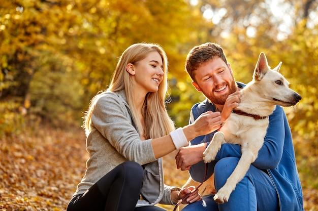 Para ubrana swobodnie, przytulając się i spacerując na łonie natury ze swoim uroczym, miłym psem