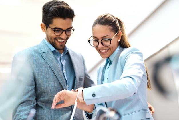 Para ubrana w garnitur, sprawdzanie nowego zegarka na rękę. kobieta jest ubranym zegarek, patrzeje i próbuje out. wnętrze sklepu technicznego.