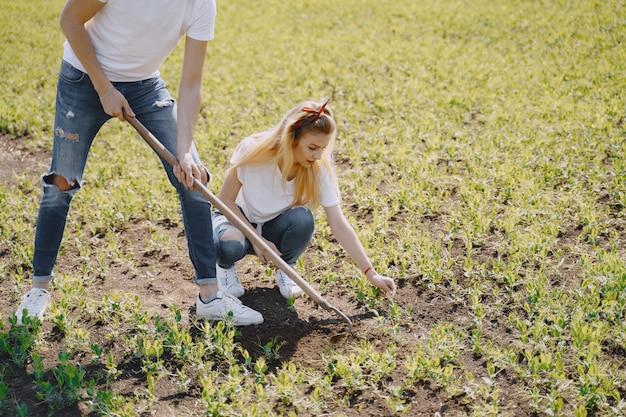 Para uprawia ziemię w rolniczym polu