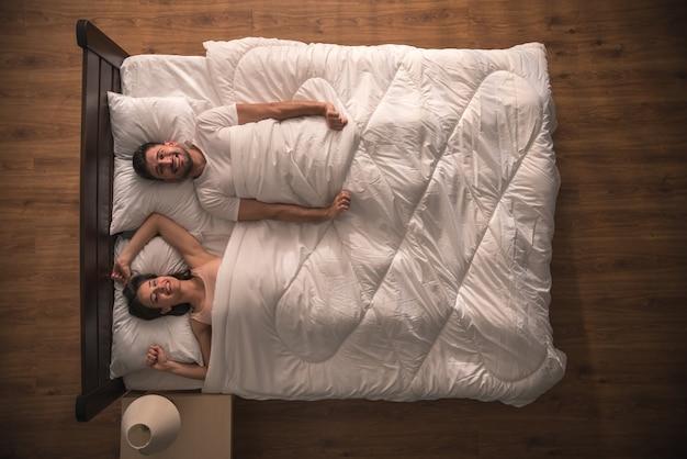 Para uśmiechnięta leżała na łóżku. widok z góry