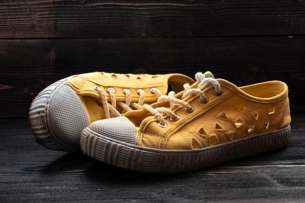 Para używanych starych butów sneakers na ciemnej powierzchni drewnianej