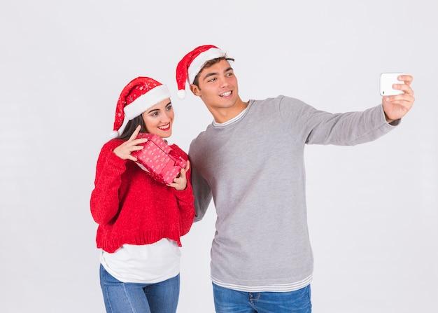 Para w bożenarodzeniowych kapeluszach bierze selfie