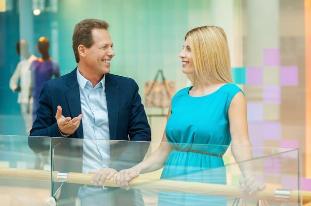 Para w centrum handlowym. wesoła dojrzała para rozmawia ze sobą stojąc w centrum handlowym