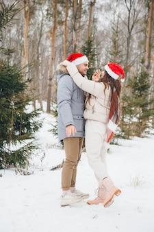 Para w czapce mikołaja, przytulająca się i wygłupiająca się w zimowym lesie iglastym