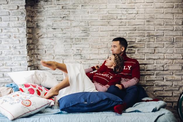 Para w czerwone swetry boże narodzenie całowanie w otoczeniu poduszek