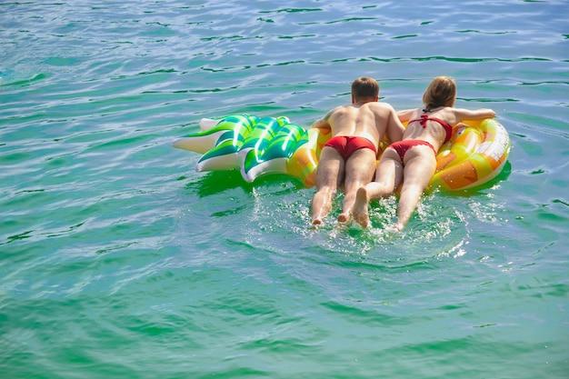 Para w czerwonych strojach kąpielowych pływająca na pływającym materacu ananasowy dmuchany materac z mężczyzną i kobietą
