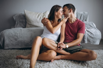 Para w domu razem siedzi na podłodze przez kanapę