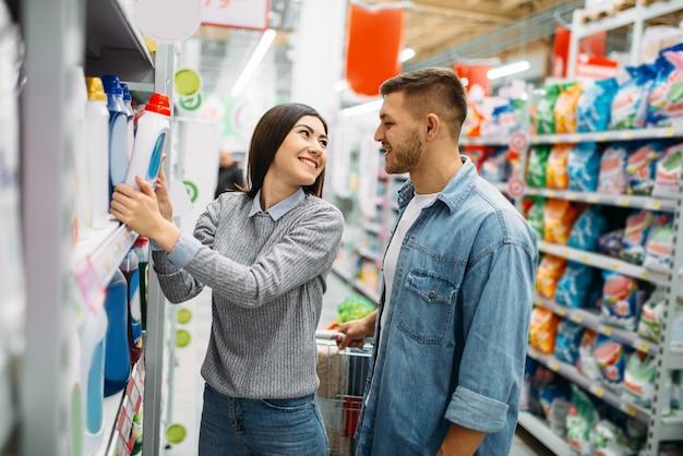 Para w dziale chemii gospodarczej, towary na półkach w supermarkecie, rodzinne zakupy. klienci w sklepie, kupujący na rynku