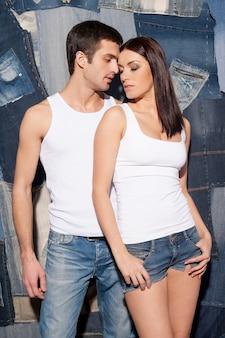 Para w dżinsach. piękna młoda para w podkoszulkach i dżinsach stojących blisko siebie i na tle dżinsów