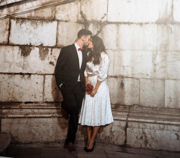Para w eleganckie ubrania, całując w ulicy wieczorem