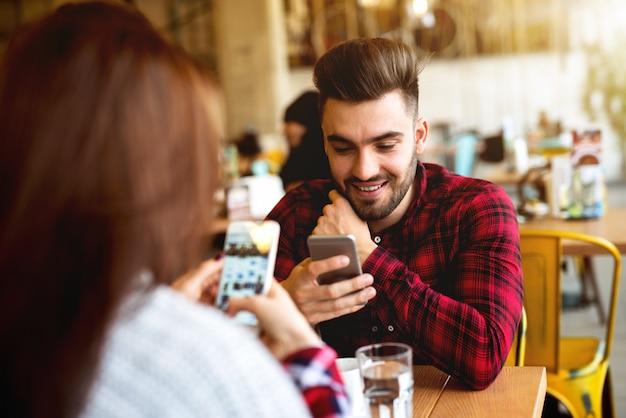 Para w kawiarni przy użyciu swoich telefonów.