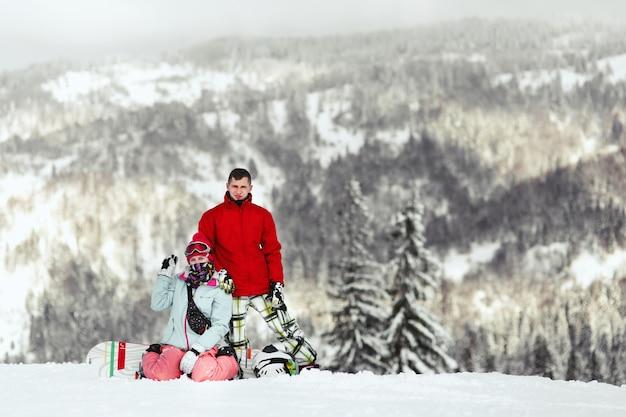 Para w kolorowych kombinezonach narciarskich pozuje na wzgórzu gdzieś w górach