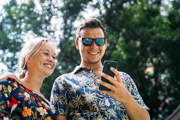 Para w kolorowych letnich kwiecistych sukienkach na ulicy z drzewami spacerującymi i patrzącymi na telefon, gdy się uśmiechają