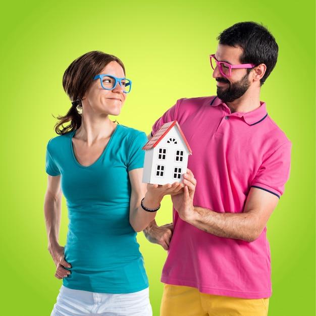 Para w kolorowych ubraniach trzyma małego dom