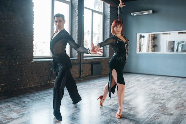 Para w kostiumach na treningu tańca ballrom w klasie.