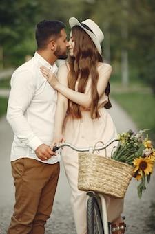 Para w letnim parku. ludzie z rocznika roweru. dziewczyna w kapeluszu.
