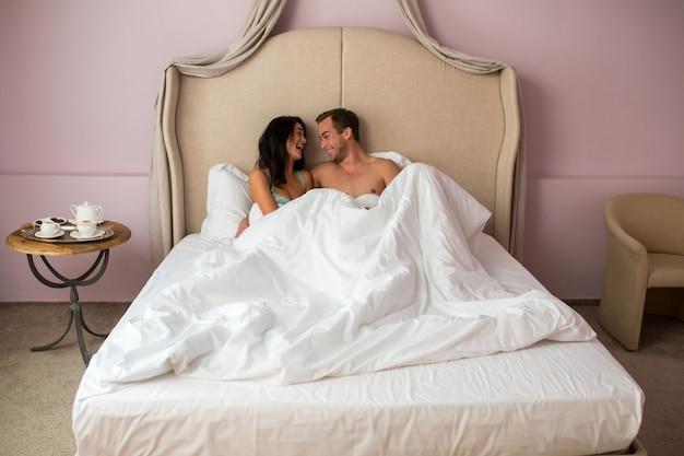 Para w łóżku śmiejąc się.