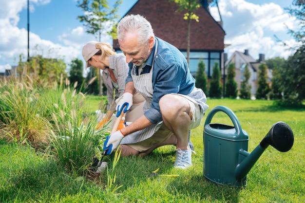 Para w ogrodzie. szczęśliwa kochająca para czuje się niesamowicie, bardzo dbając o swoje kwietne otoczenie