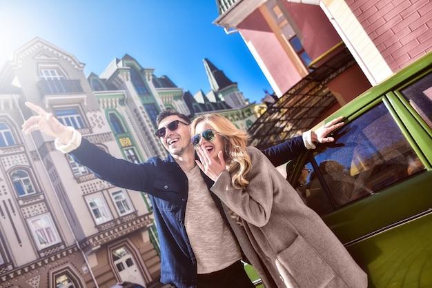 Para w okularach przeciwsłonecznych stojących w pobliżu samochodu i szukających nowego mieszkania