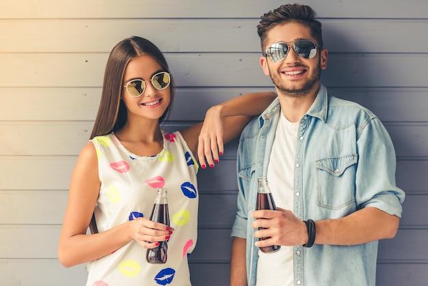 Para w okularach słonecznych, trzymając butelkę wody sodowej