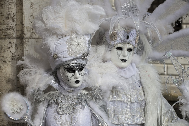 Para w pięknych sukienkach i tradycyjnych weneckich maskach podczas słynnego na całym świecie karnawału