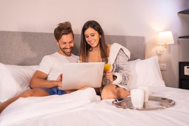 Para w piżamie szukająca hoteli lub wycieczek z komputera na śniadanie w hotelowym łóżku, styl życia zakochanej pary.