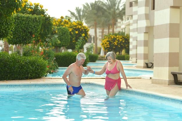 Para w podeszłym wieku pływająca w basenie w ośrodku hotelowym?