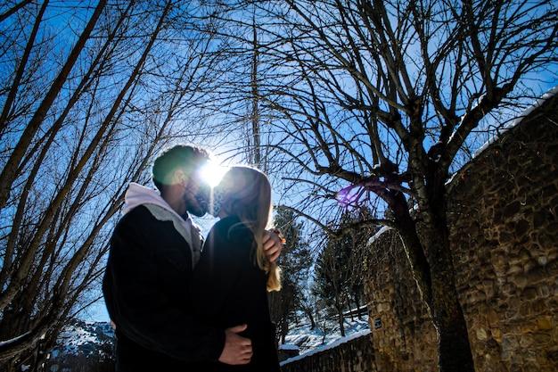 Para w śniegu w słoneczny dzień w lesie z drzewami i błękitnym niebem