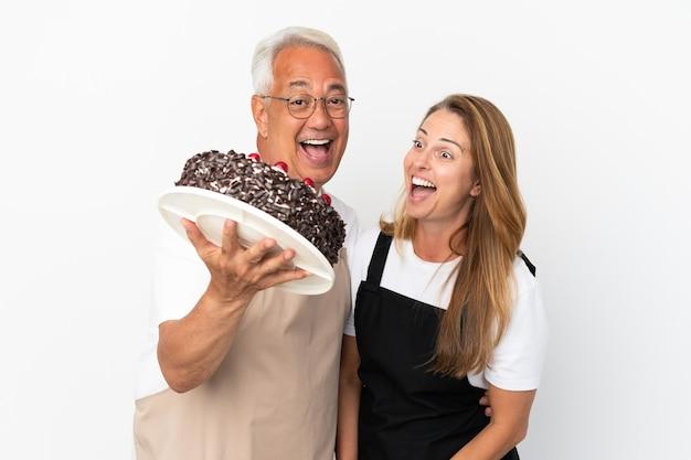 Para w średnim wieku kucharz trzyma tort urodzinowy na białym tle