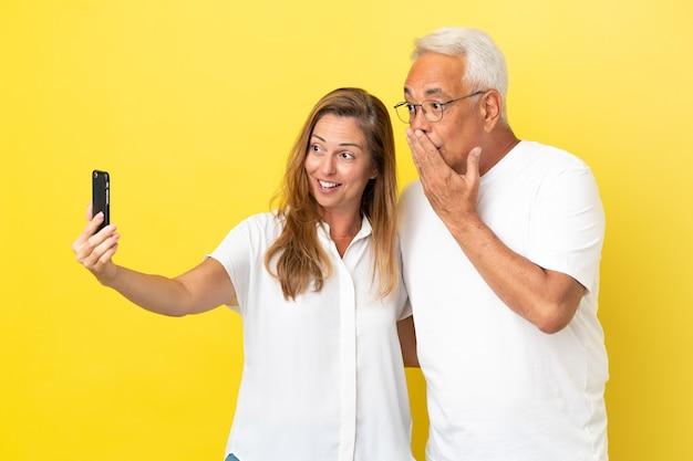 Para w średnim wieku na żółtym tle robi selfie za pomocą telefonu komórkowego