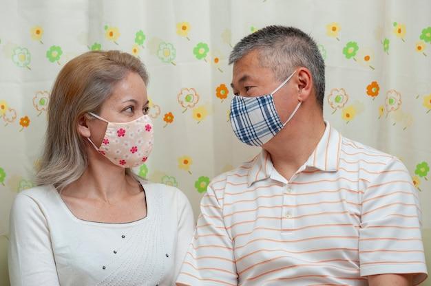 Para w średnim wieku siedzi patrząc na siebie na sobie maskę tkaniny