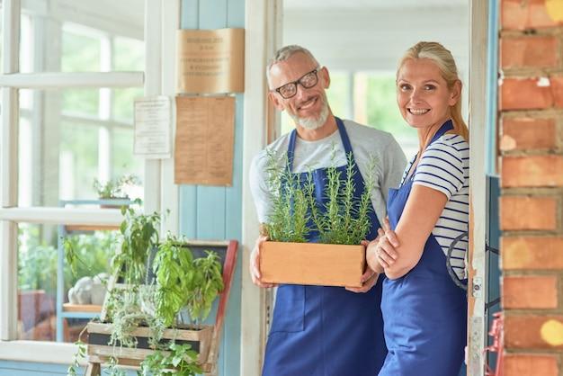 Para w średnim wieku stojąca w drzwiach domu ogrodowego