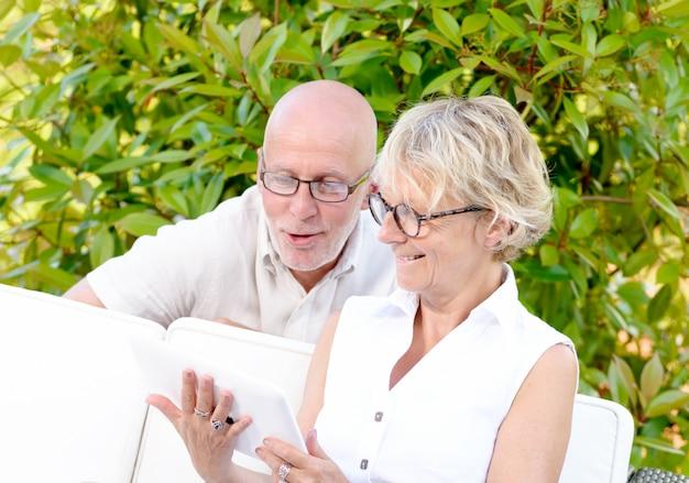 Para w średnim wieku, uśmiechnięta, za pomocą tabletu w ogrodzie