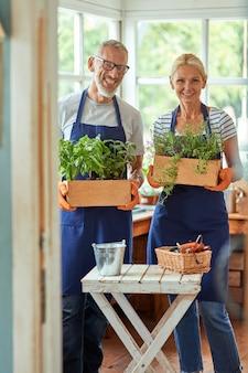 Para w średnim wieku z rosnącymi roślinami w szklarni