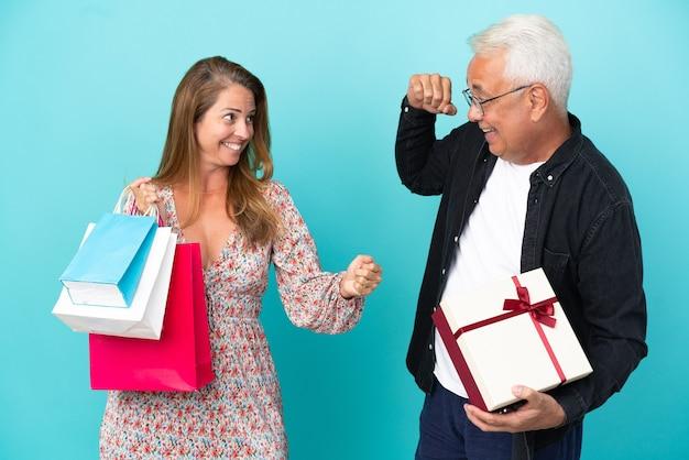 Para w średnim wieku z torbą na zakupy i prezentem na białym tle na niebieskim tle świętująca zwycięstwo w pozycji zwycięzcy