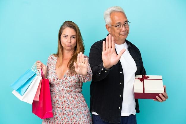 Para w średnim wieku z torbą na zakupy i prezentem na białym tle na niebieskim tle, wykonując gest zatrzymania, zaprzeczający sytuacji, która myśli źle