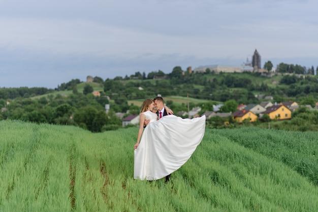 Para w stroju ślubnym stoi na zielonym polu na tle wioski o zachodzie słońca, młodej pary. pan młody nosi ukochaną w swoich ramionach.