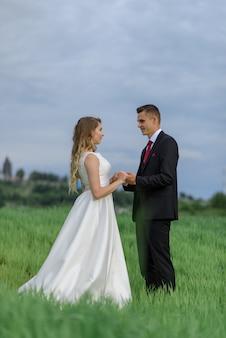 Para w stroju ślubnym stoi na zielonym polu na tle wioski o zachodzie słońca, państwo młodzi