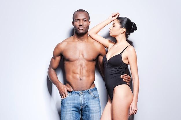 Para w stylu. piękna młoda para rasy mieszanej stojąca blisko siebie i na szarym tle
