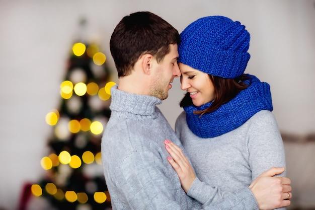 Para w swetrach przytula się razem w wigilię niewyraźne girlandy na tle